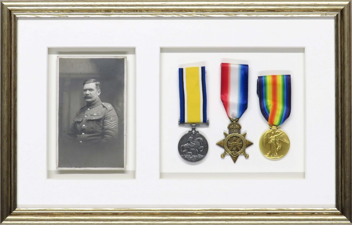 A beautiful gold frame to house a set of medals alongside a photograph of a soldier