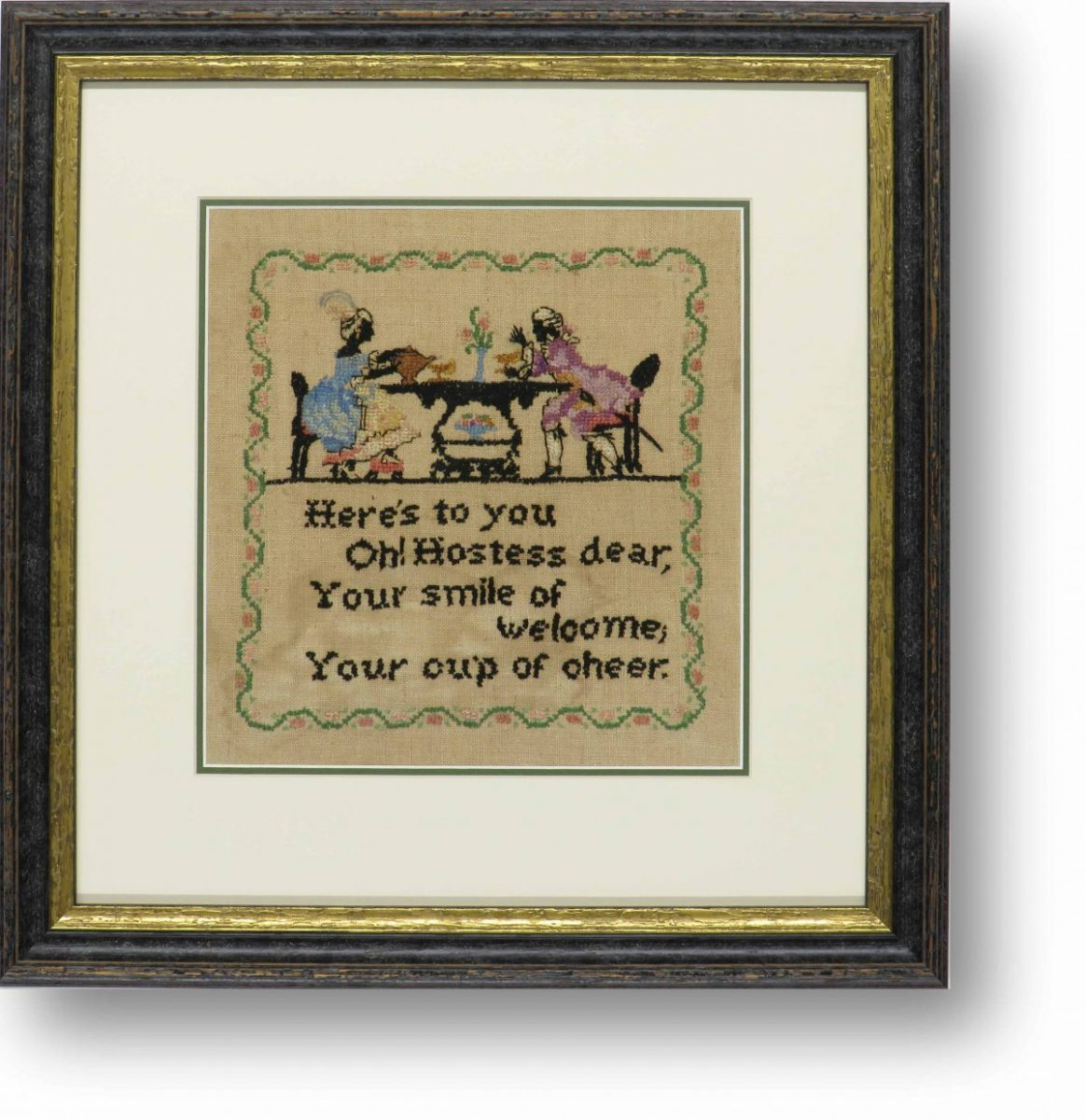 A framed piece of heirloom embroidery in a black and gilt frame